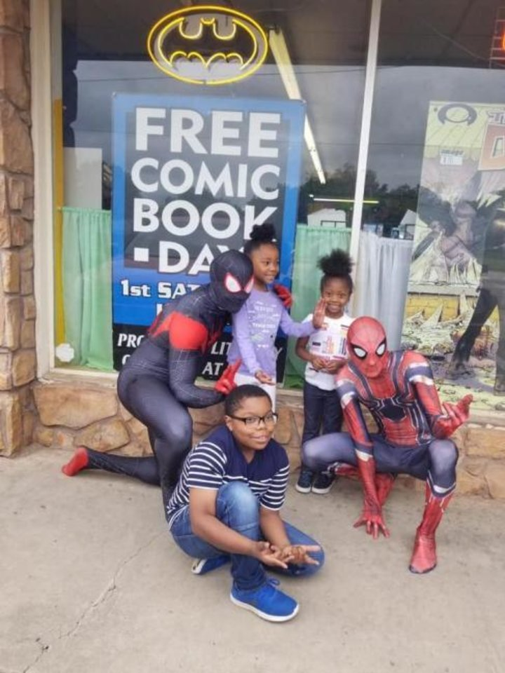 Photo -  Kids pose with Spiderman at the Free Comic Book Day in Norman. [Provided]