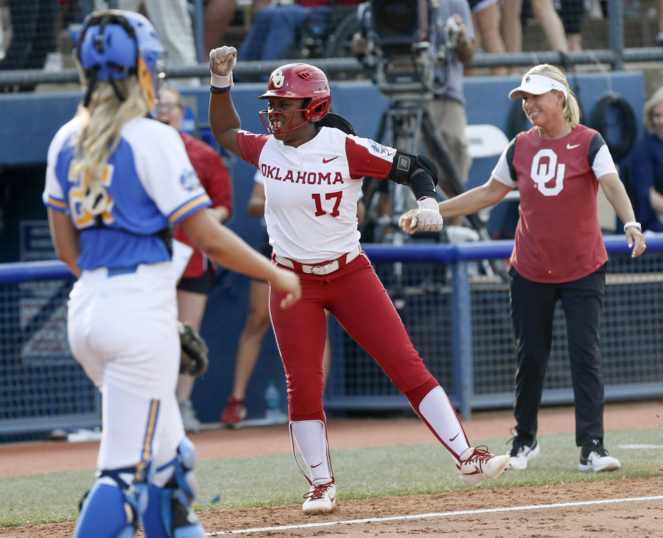 Photo - OU's Shay Knighten (17) celebrates as she runs home past coach Patty Gasso, right, and UCLA catcher Paige Halstead (25) after hitting a home run in the second inning during the first NCAA softball game in the championship series of the Women's College World Series between Oklahoma and UCLA at USA Softball Hall of Fame Stadium in Oklahoma City, Monday, June 3, 2019. [Nate Billings/The Oklahoman]