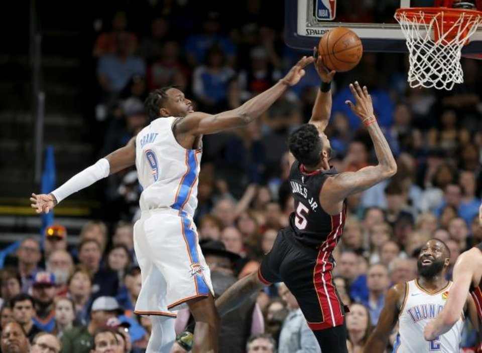 Photo -  Oklahoma City's Jerami Grant, left, tries to disrupt a shot by Miami's Derrick Jones Jr. during Monday night's game at Chesapeake Energy Arena. [Bryan Terry/The Oklahoman]