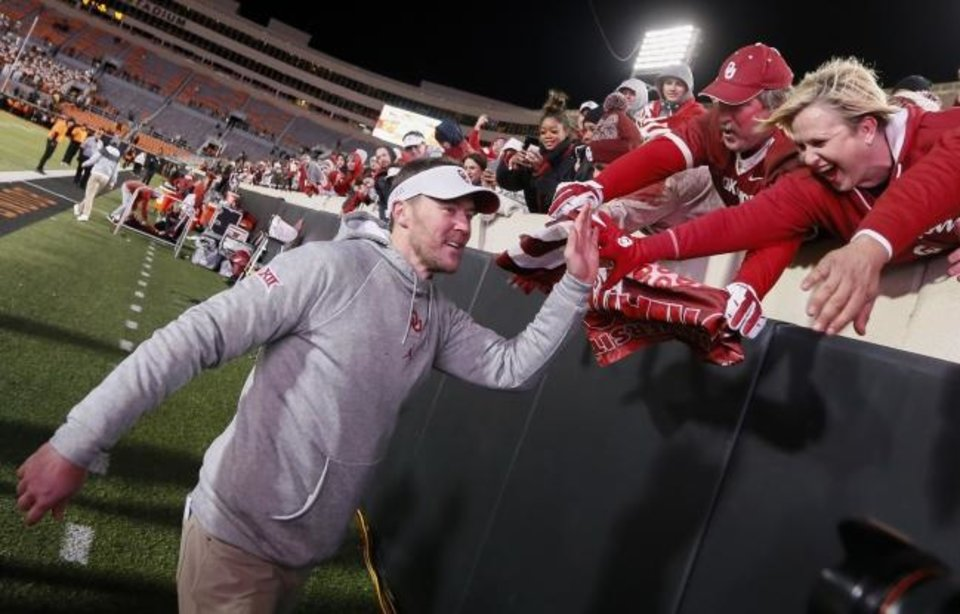 Photo -  Oklahoma coach Lincoln Riley celebrates with fans after beating Oklahoma State 34-16 last weekend in Stillwater. [Nate Billings/The Oklahoman]