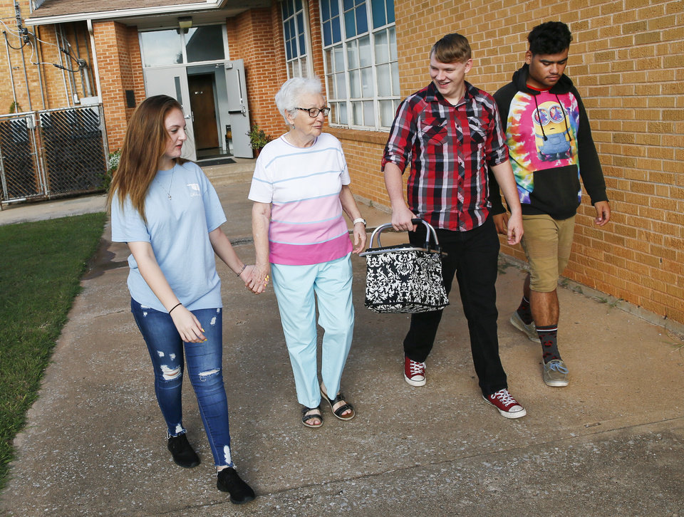 Photo - Volunteer Neva Kitsmiller, second from left, is walked home by students, from left, Raegan Wylie, 15, of Comanche, Chance Taylor, 18, of Duncan, and Adam Stedman, 17, of Comanche, after Kitsmiller taught crochet at FAME Academy, an alternative school in Comanche Public Schools, in Meridian, Okla., Wednesday, Oct. 3, 2018. Photo by Nate Billings, The Oklahoman