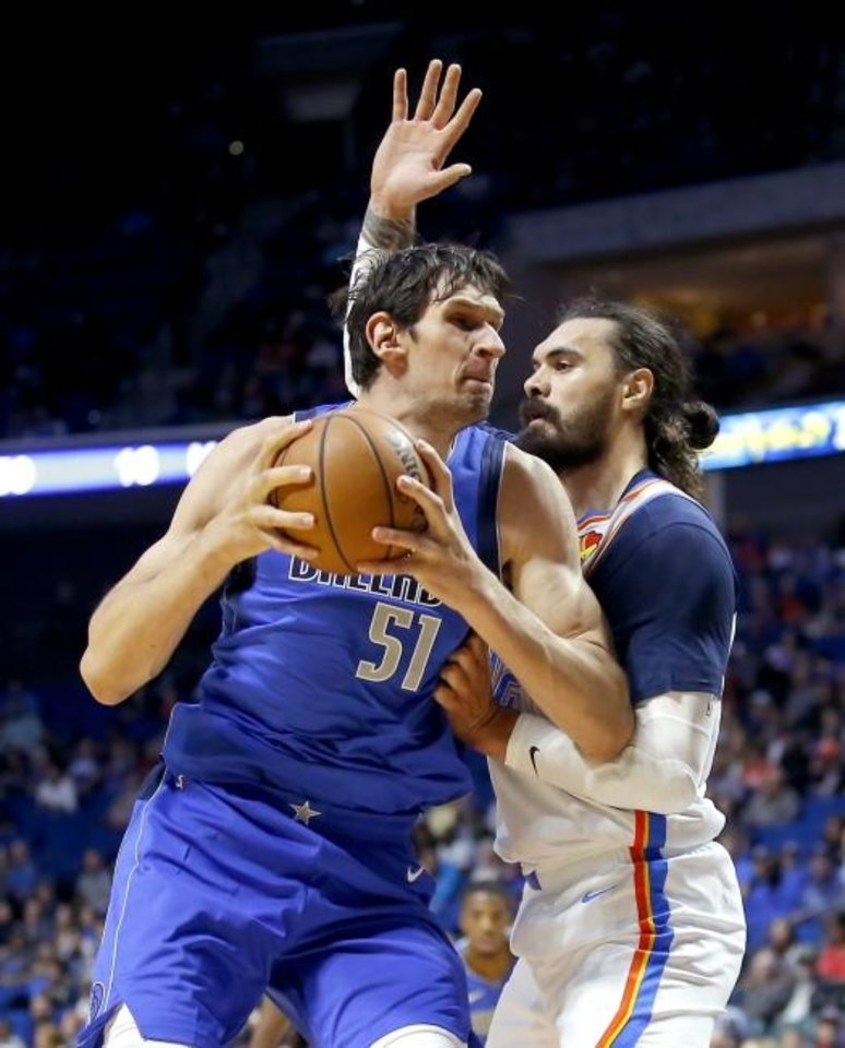 Photo -  Oklahoma City's Steven Adams, right, defends Dallas' Boban Marjanovic during Tuesday night's preseason game in Tulsa. Adams set the tone early with a 3-pointer. The Thunder won the game 119-104. [Sarah Phipps/The Oklahoman]