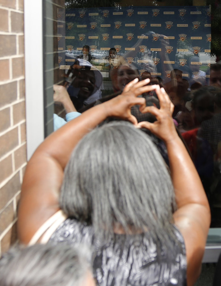 Photo - A woman holds up a heart sign in the window outside of the press conference. Russell Westbrook returns to sign an extension of his contract and is greeted by hundreds of Thunder fans outside of the Chesapeake Arena, Thursday, August 4, 2016. Photo by Doug Hoke, The Oklahoman