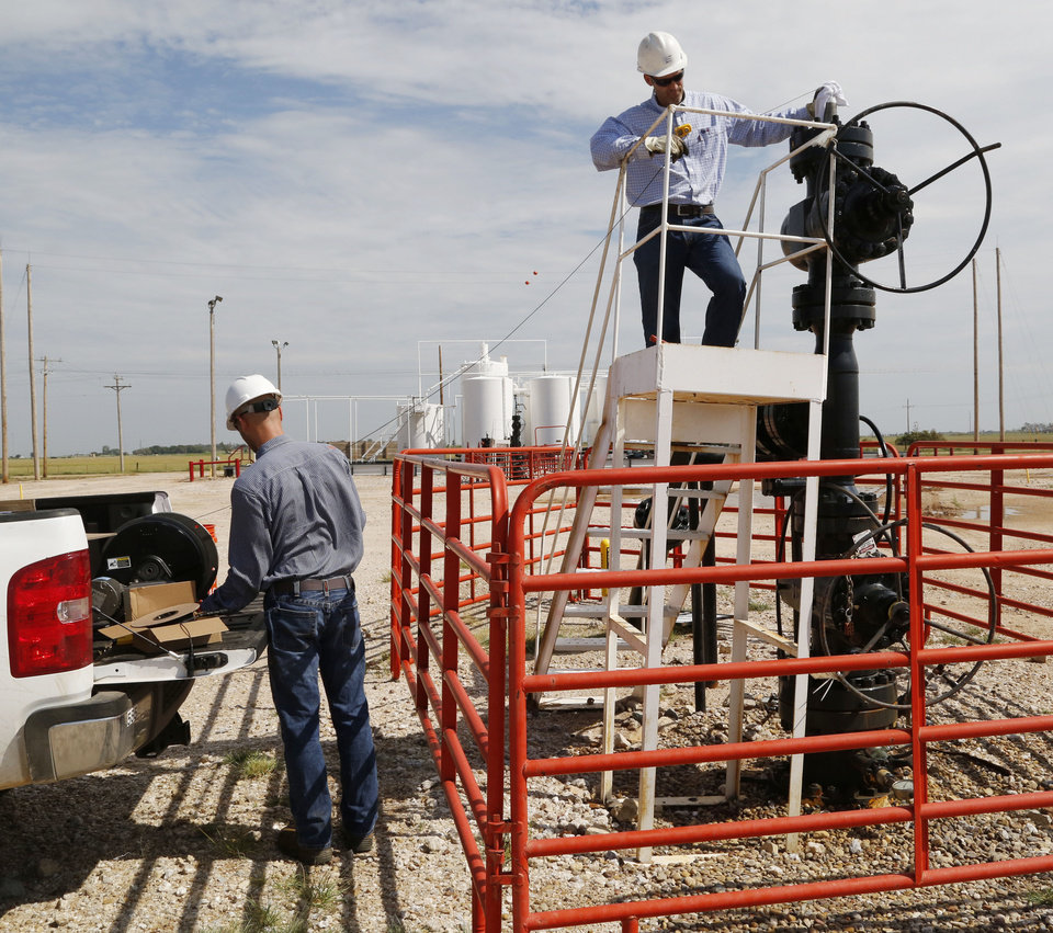 Photo -  Curtis Smith, left, and Kyle Murray, with the Oklahoma Geological Survey, insert testing equipment through the top of an inactive wastewater disposal well Wednesday near Cherokee. [Photo By Paul Hellstern, The Oklahoman]