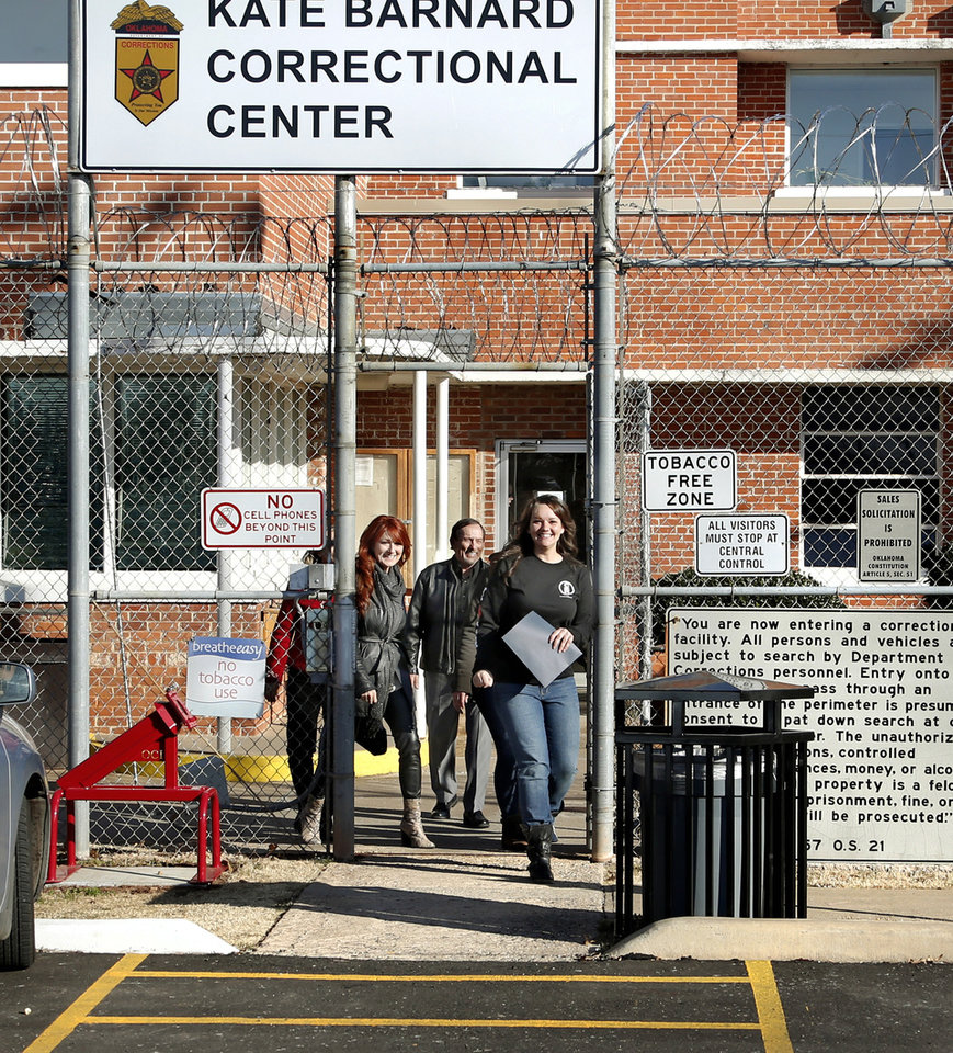Photo - Department of Corrections inmate Kayla Jeffries, right,  flashes a big smile while walking through the 10-foot-high security gate as she leaves prison Wednesday afternoon. Jeffries traded her orange prison uniform for freedom as she walked out of the Kate Barnard Correctional Center accompanied not by guards, but alongside her dad, stepmother and older sister Wednesday afternoon, Dec. 5, 2018. Earlier in the day, Gov. Mary Fallin commuted her 20-year prison sentence. The 26-year-old mother of two from Grove, Okla., was one of 21 Oklahoma inmates who had their sentences commuted to time served.  Inmates granted commutations were serving sentences 10 years or longer for drug possession and other crimes that now carry lesser punishments following recent reforms approved by voters and state lawmakers. The inmates were assisted through a commutation campaign led by Oklahomans for Criminal Justice Reform.  Photo by Jim Beckel, The Oklahoman.