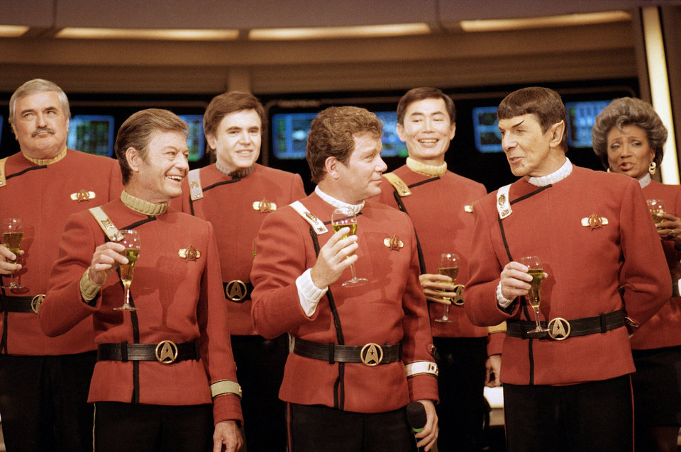 "Photo - FILE- In this Dec. 28, 1988, file photo shows members of the ""Star Trek"" crew, from left, Nichelle Nichols, Leonard Nimoy, George Takei,  William Shatner, Walter Koenig,  DeForest Kelley and James Doohan, toast the newest ""Star Trek"" film during a news conference at Paramount Studios. (AP Photo/Bob Galbraith,File)"