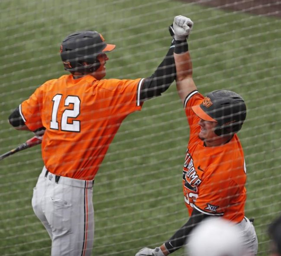 Photo -  Oklahoma State's Trevor Boone (33) celebrates with Carson McCusker (12) after hitting a home run during the second inning in Game 3 against Texas Tech on Sunday in Lubbock. [AP Photo/Brad Tollefson]