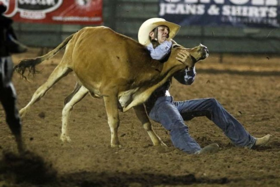 Photo -  Gus Gaillard, Morse, Texas, grabs onto a steer in the steer wrestling event Sunday at the International Finals Youth Rodeo  at the Heart of Oklahoma Exposition Center in Shawnee. [Paxson Haws/The Oklahoman]