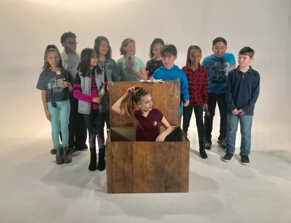 Photo -  Apollo Elementary School teacher Deya Jacobs and a group of fifth-graders, including Mia Jackson in a box, prepare to tape a video about the Henry