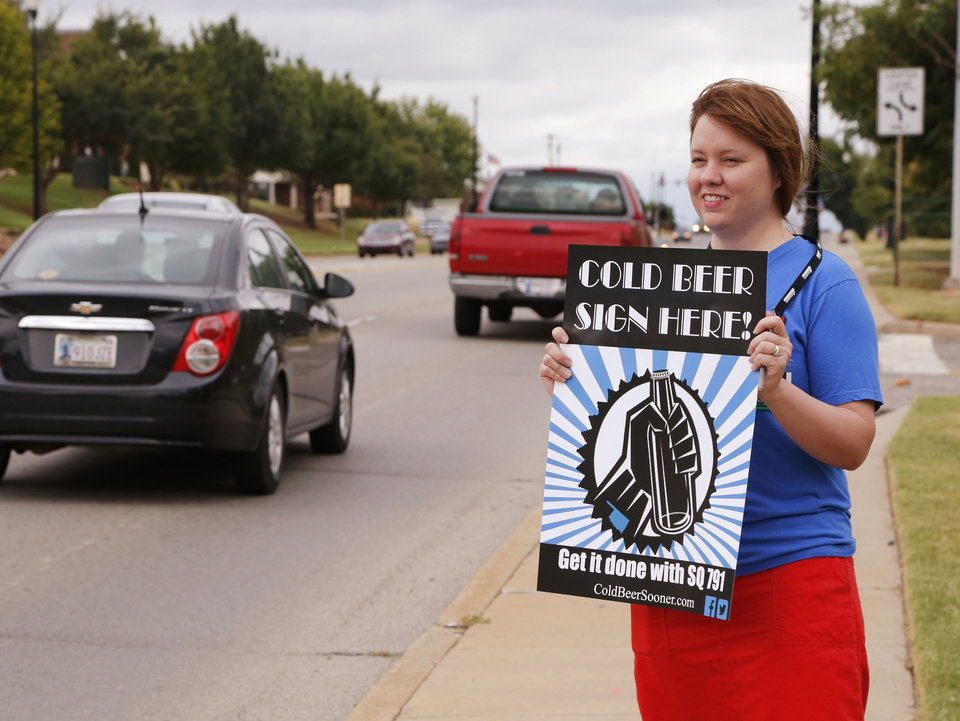 Photo - Amie Hendrickson encourages drivers to stop, as liquor store owners hold a petition drive for signatures on State Question 791 at Fink Park in Edmond, Okla. Saturday, Aug. 20, 2016.  Photo by Paul Hellstern, The Oklahoman