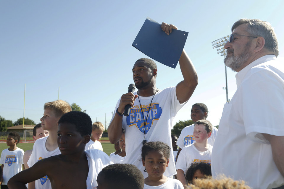 "Photo - Los Angeles Chargers player Jeff Richards talks to the crowd after the declaration of July 13th as ""Jeff Richards Day"" in Del City as his elite football camp at Del City High School in Del City, Oklahoma on July 13, 2019. [Paxson Haws/The Oklahoman]"