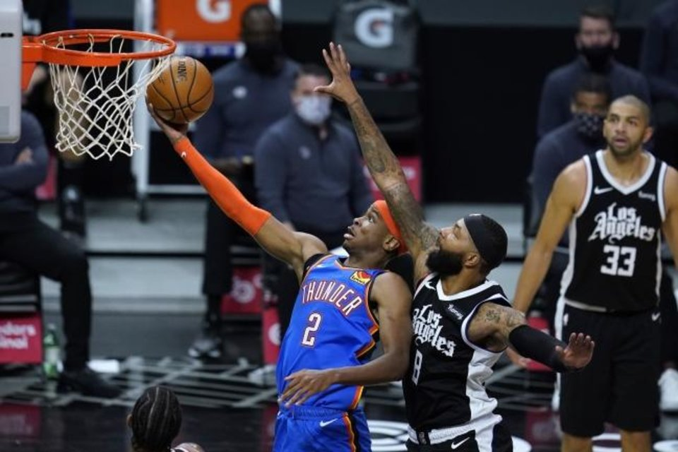 Photo -  Thunder guard Shai Gilgeous-Alexander (2) goes for a layup past Clippers forward Marcus Morris Sr. (8) during the fourth quarter of a 120-106 loss Friday night in Los Angeles. [AP Photo/Ashley Landis]