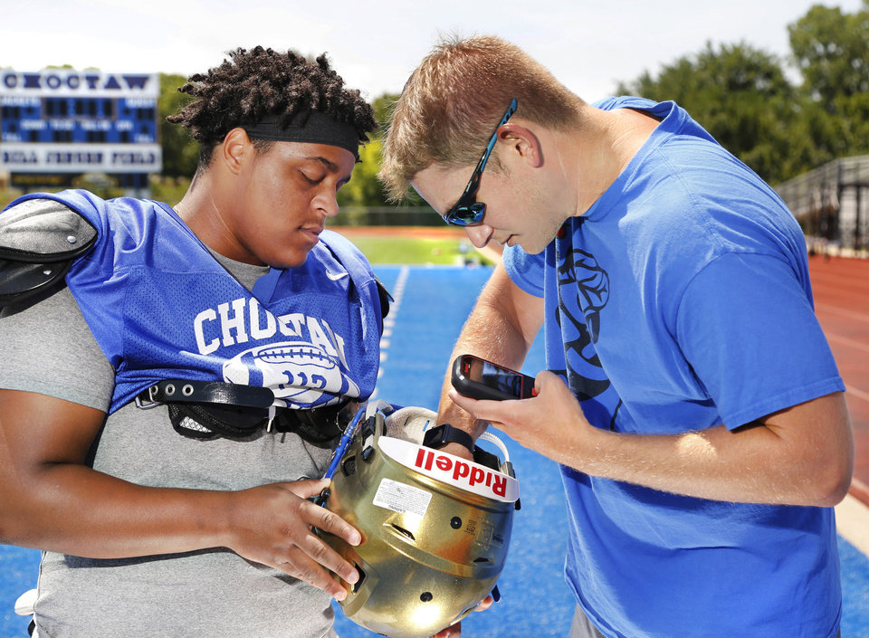 Photo -  Choctaw athletic trainer Robert Polk makes an adjustment to a sensor inside the helmet worn by senior defensive lineman Jaoni Thayer at the start of an August practice. [PHOTO BY JIM BECKEL, The Oklahoman]