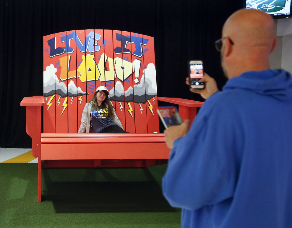 Photo - Thunder fan Elena Shortey has her picture taken in a giant chair by her stepfather, Shawn Ingram, before an NBA basketball game between the Oklahoma City Thunder and the Washington Wizards at Chesapeake Energy Arena in Oklahoma City, Friday, Oct. 25, 2019. [Nate Billings/The Oklahoman]