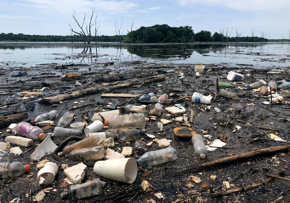 Photo -  Styrofoam cups, plastic bottles and debris from Oklahoma City and Edmond covers the shoreline at Carl Reherman Park after heavy rain. Lake officials said cleanup is a constant battle with no clear solution in sight. [Photo by Kelsy Schlotthauer, The Oklahoman]