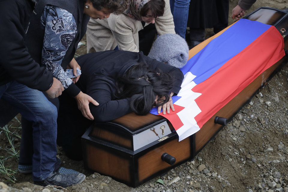 Photo -  Relatives of Mkhitar Beglarian, an ethnic Armenian soldier of Nagorno-Karabakh army who was killed during a military conflict, mourn during his funeral at a cemetery in Stepanakert, the separatist region of Nagorno-Karabakh, on Sunday, Nov. 15, 2020. Ethnic Armenian forces had controlled Nagorno-Karabakh and sizeable adjacent territories since the 1994 end of a separatist war. Fighting resumed in late September and have now ended with an agreement that calls for Azerbaijan to regain control of the outlying territories as well as allowing it to hold on to parts of Nagorno-Karabakh that it seized during the fighting. (AP Photo/Sergei Grits)