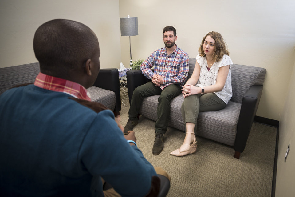 Photo - OBU MFT students Scott Pfister (seated on couch, left) and Hannah Mire visit with fellow student Ronald Assimwe (left) in one of the therapy rooms inside OBU's new Marriage and Family Therapy Clinic. Photo provided by OBU.