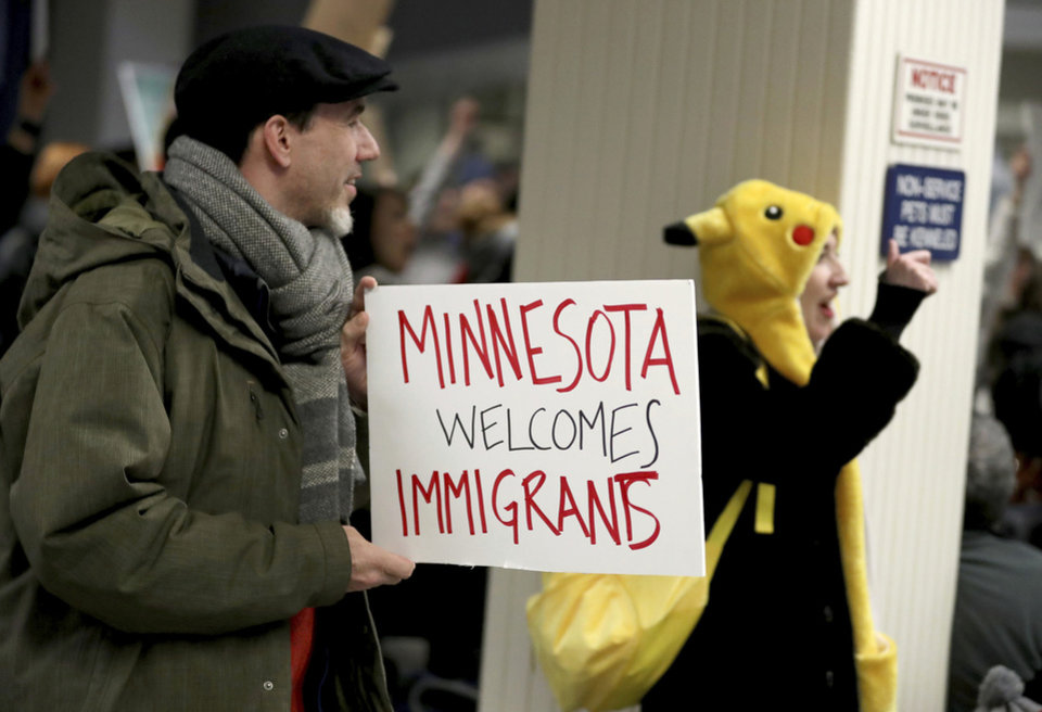 Photo - Adrian Hegeman, of St. Paul, holds a sign while joining other opponents to new immigration restrictions to protest an executive order signed by President Donald Trump, restricting immigration from several Muslim nations Saturday, Jan. 28, 2017, at the Minneapolis-St. Paul International Airport, in Minneapolis. (David Joles/Star Tribune via AP)