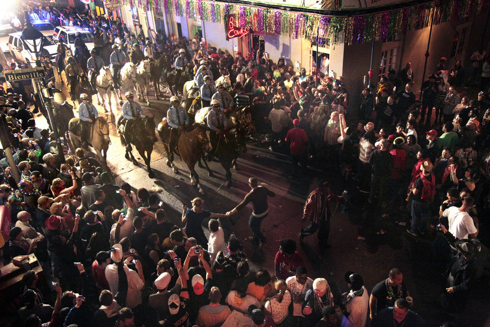 Photo -  File - In this March 9, 2011 file photo, police on horseback and foot clear out the crowds on Bourbon Street at midnight for the end of Mardi Gras festivities in New Orleans. The final weekend of Mardi Gras season in New Orleans has begun with a warning from police that crowds won't be tolerated as the city fights to stop the spread of the coronavirus. Police chief Shaun Ferguson noted Friday, Feb. 12, 2021, that bars throughout the city were being ordered to close through Fat Tuesday. And he said police will man barricades limiting pedestrian traffic on Bourbon Street to people who live or work there, hotel guests, and restaurant patrons. T (AP Photo/Gerald Herbert, File)