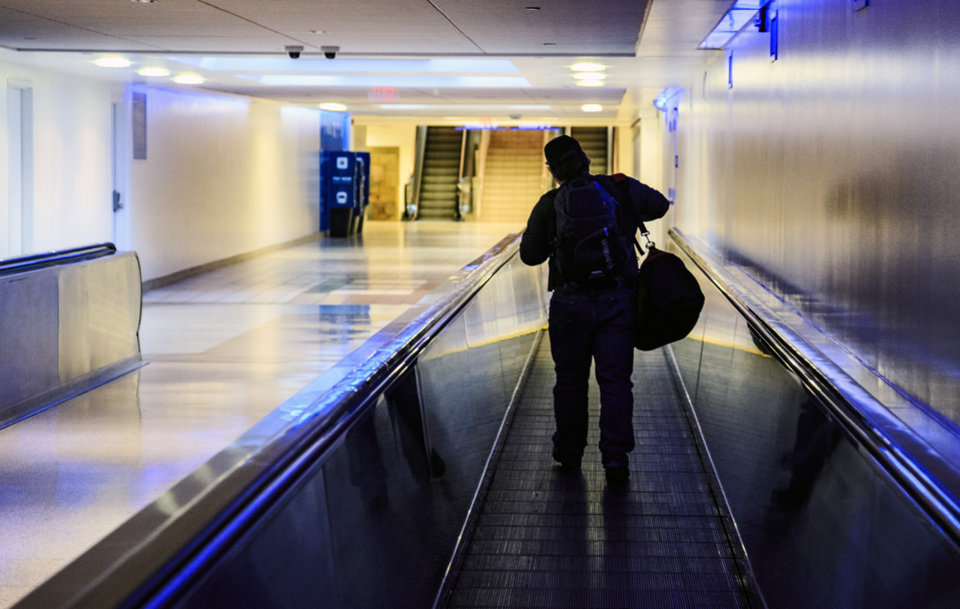 Photo -  Suitcase slung over his shoulder, a man heads toward the terminal at Will Rogers World Airport on Monday.