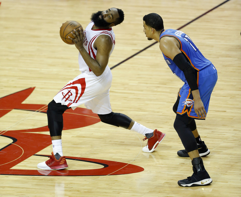 Photo - Oklahoma City's Andre Roberson (21) defends Houston's James Harden (13) during Game 2 in the first round of the NBA playoffs between the Oklahoma City Thunder and the Houston Rockets in Houston, Texas,  Wednesday, April 19, 2017.  Photo by Sarah Phipps, The Oklahoman