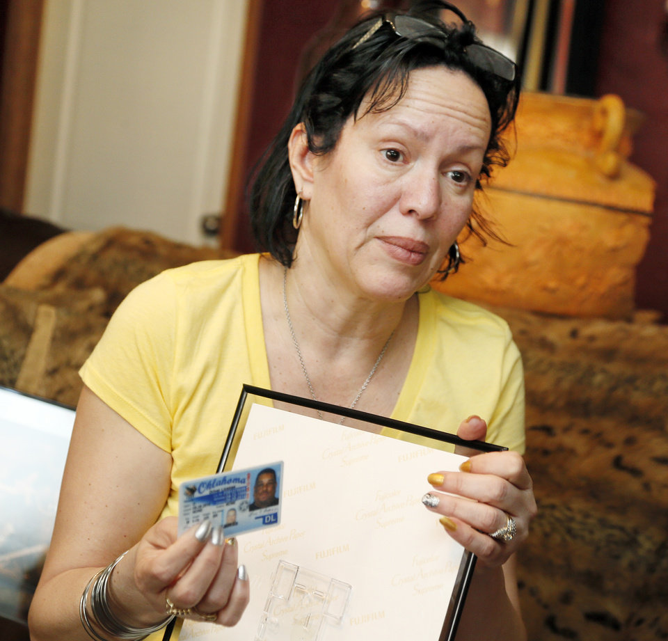 Photo - Nair Rodriguez talks about her husband Luis Rodriguez while holding his driver's license at the Rodriguez family's home in Norman, Okla., Monday, Feb. 17, 2014.  Luis Rodriguez died during an incident with Moore police at the Warren Theatre, Friday, Feb. 14, 2014. Photo by Nate Billings, The Oklahoman