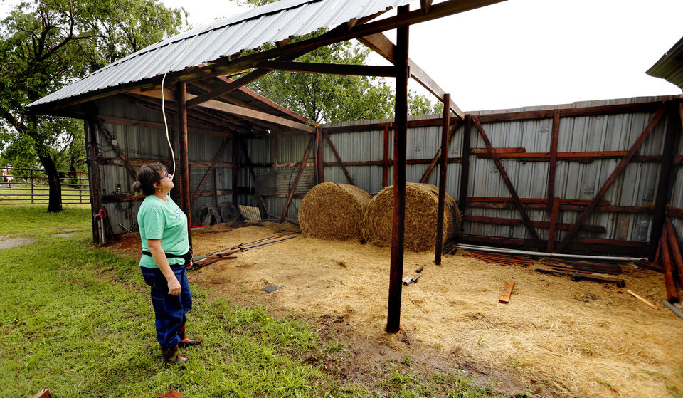 Photo - Kris Glover stands beside Mary Flueckiger's (her mother's) barn on Thursday, May 3, 2018 in Purcell, Okla..  Flueckiger lost several outbuildings and trees but her horses escaped uninjured.   Photo by Steve Sisney, The Oklahoman