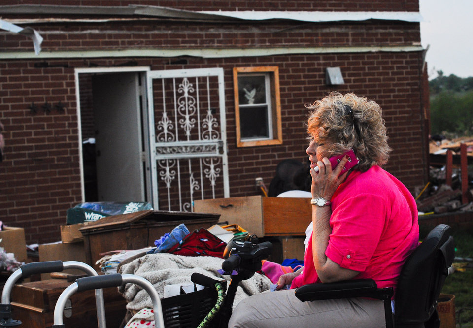 Photo - Janee Keiser, 66 of Carney, talks to her son on the phone while sitting outside of her house that was destroyed when a tornado went through Carney, Okla. on May 19, 2013.  KT King/For the Oklahoman