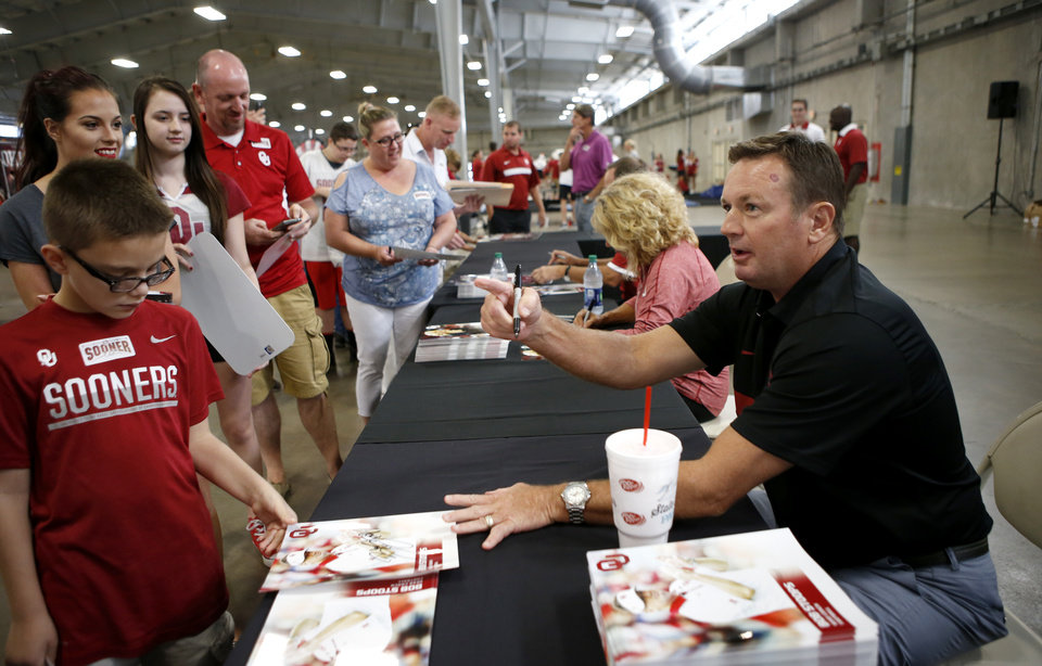 Photo - Oklahoma football coach Bob Stoops signs autographs during the Sooner Sports Experience at the Cox Pavilion at State Fair Park in Oklahoma City, Thursday, August 4, 2016. Photo by Bryan Terry, The Oklahoman