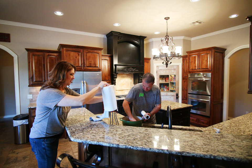 Photo -  Sharla and Dan Bradley do last-minute prep work on their home at 9852 W Charter Oak Road just before it hit the market on May 4 for $1. [PHOTO BY DOUG HOKE, THE OKLAHOMAN]
