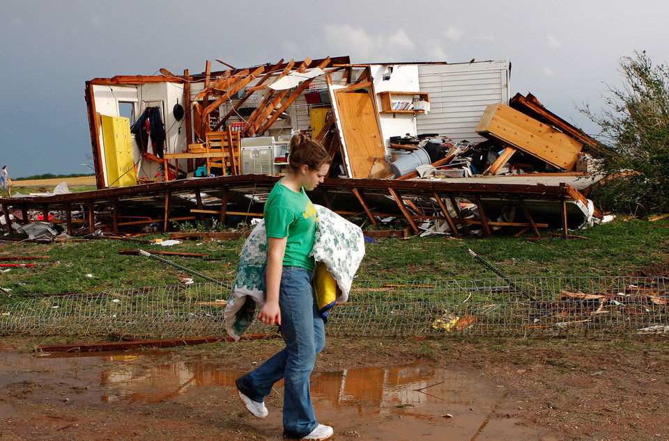 Photo - Rebecca Apel, 15,carries a blanket she retrieved from the rubble of her family's home and walks to a nearby van where salvageable belongings were placed.  Her home on SH 74 near Cashion was ripped apart by a tornado lateTuesday afternoon,  May 24, 2011,   No one was inside the house and there were no injuries. Photo by Jim Beckel, The Oklahoman