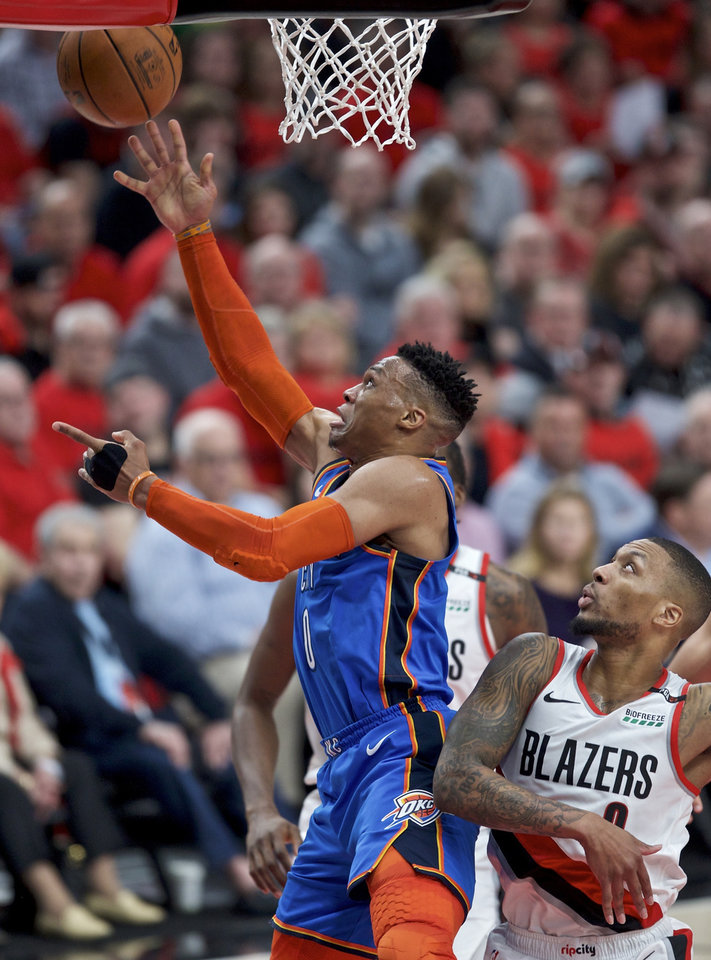 Photo - Oklahoma City Thunder guard Russell Westbrook, left, shoots next to Portland Trail Blazers guard Damian Lillard during the first half of Game 2 of an NBA basketball first-round playoff series Tuesday, April 16, 2019, in Portland, Ore. (AP Photo/Craig Mitchelldyer)