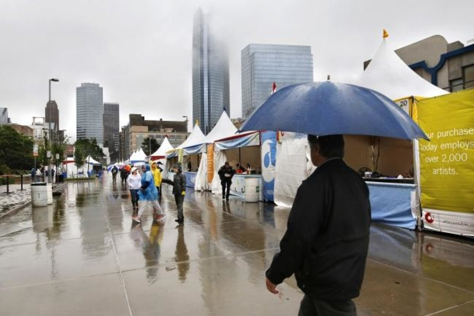 Photo -  A few visitors tolerate a rain shower as they stroll past food tents on the south side of Civic Center on the opening day of the Festival of the Arts. The weather is expected to improve as the event continues through Sunday.