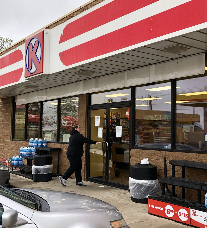 Photo -  An individual walks back inside a closed Circle K at 1101 W Memorial Road after moving items outside. The store is closed, and several people were working inside to remove inventory from shelves. [PHOTOS BY DAVID DISHMAN, THE OKLAHOMAN]