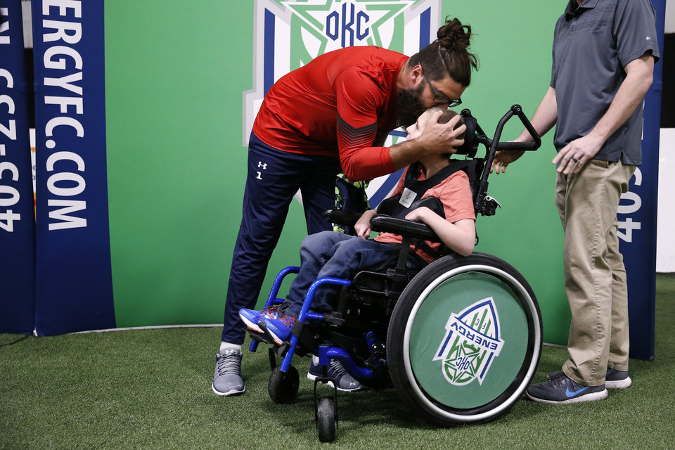 Photo -  Energy FC goalkeeper Cody Laurendi plants a kiss on the head of Sidekick buddy Jackson Wells during an event last month in Oklahoma City. [PHOTO BY BRYAN TERRY, THE OKLAHOMAN]