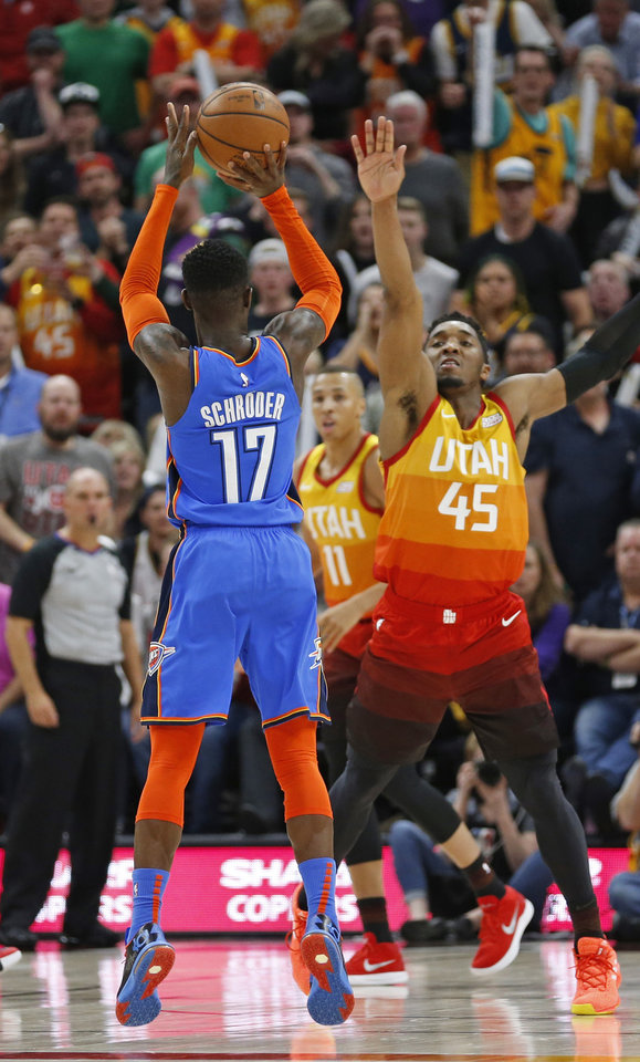 Photo - Oklahoma City Thunder guard Dennis Schroder (17) shoots as Utah Jazz guard Donovan Mitchell (45) defends in the second half during an NBA basketball game, Monday, March 11, 2019, in Salt Lake City. (AP Photo/Rick Bowmer)