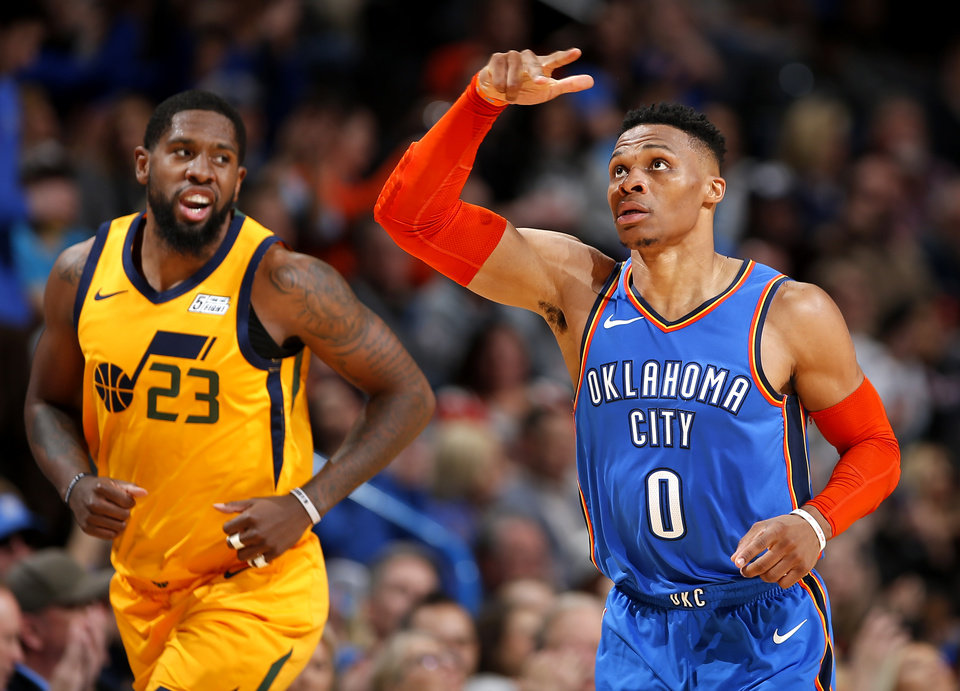 Photo - Oklahoma City's Russell Westbrook (0) celebrates a 3-point basket in front of Utah's Royce O'Neale (23) during the NBA game between the Oklahoma City Thunder and the Utah Jazz at the Chesapeake Energy Arena, Friday, Feb. 22, 2019. Photo by Sarah Phipps, The Oklahoman