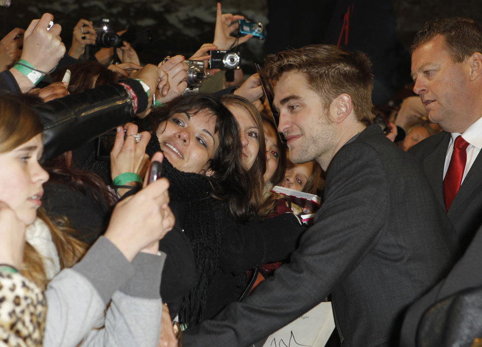 Photo - British actor Robert Pattinson poses for fans as he arrives at the UK film premiere of 'Twilight Breaking Dawn Part 1' at Westfield Stratford in east London, Wednesday, Nov. 16, 2011. (AP Photo/Joel Ryan) ORG XMIT: LENT110