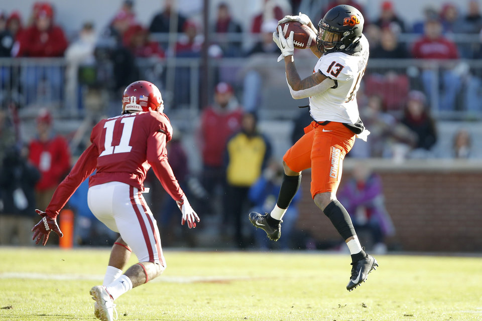 Photo - Oklahoma State's Tyron Johnson (13) catches the ball beside Oklahoma's Parnell Motley (11) during a Bedlam college football game between the University of Oklahoma Sooners (OU) and the Oklahoma State University Cowboys (OSU) at Gaylord Family-Oklahoma Memorial Stadium in Norman, Okla., Nov. 10, 2018.  Photo by Bryan Terry, The Oklahoman