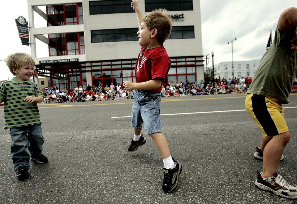 Photo - Samuel Shoop, age 3, (left) watches as Alan Devero, age 4, (center) and Caden Ball (right) dance in the street during the Oklahoma Centennial Parade in Oklahoma City on Sunday, Oct. 14, 2007. By John Clanton, The Oklahoman