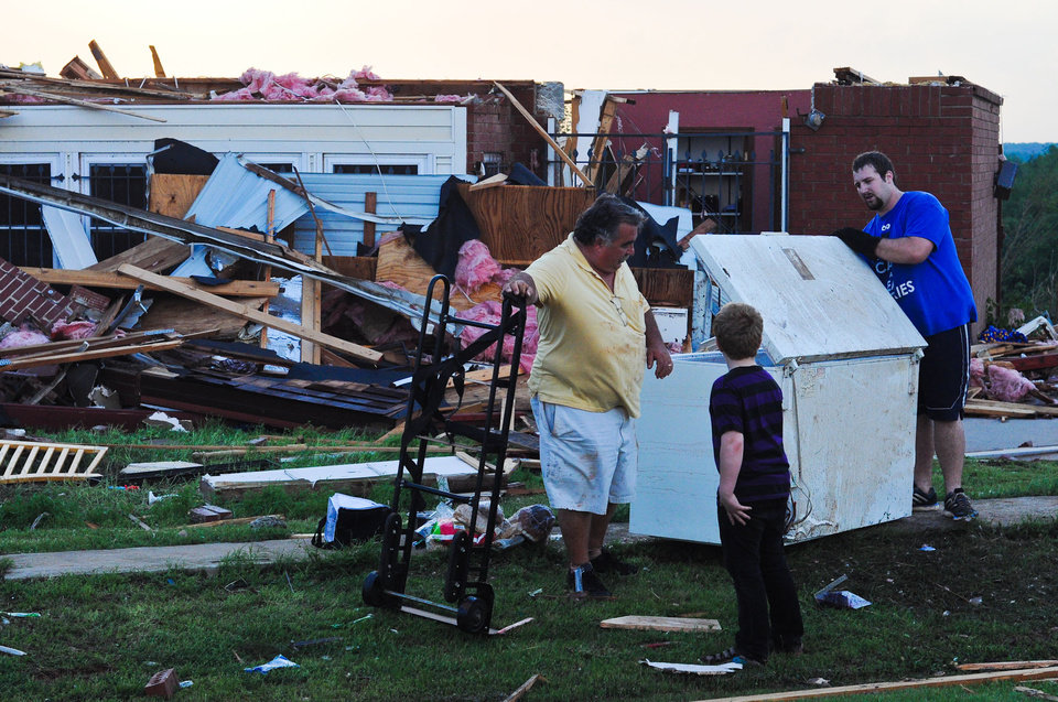 Photo - Steve Wilson (left) and Austin Perdue (right) carry a freezer out of a destroyed house while 10-year-old Camden Allen looks on. The house destroyed was by the May 19, 2013 tornado that went through Carney, Okla.  KT King/For the Oklahoman