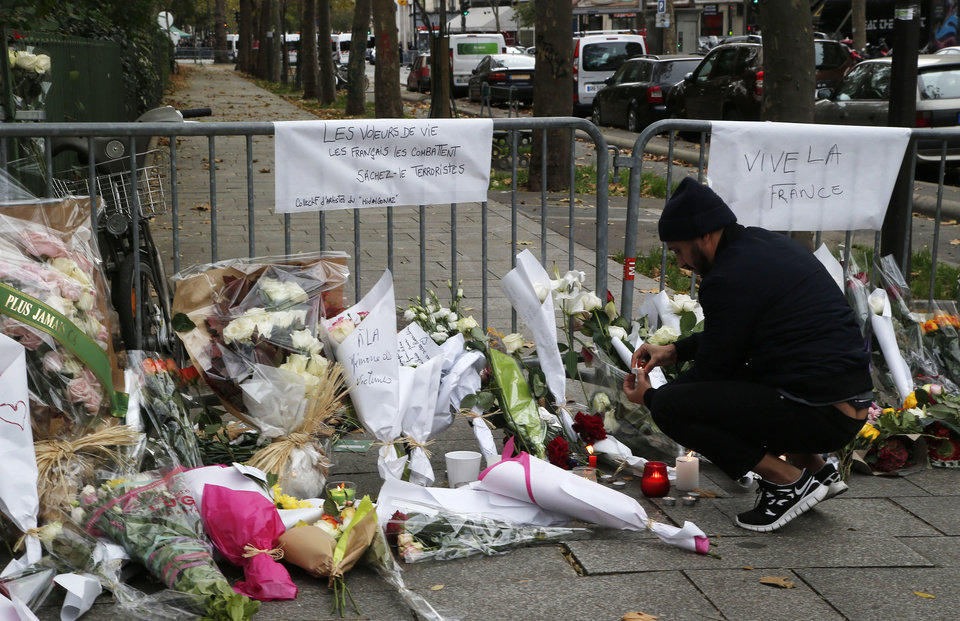 Photo - A man lights up a candle outside the Bataclan theater in Paris, Saturday, Nov. 14, 2015. rench President Francois Hollande vowed to attack the Islamic State group without mercy as the jihadist group claimed responsibility Saturday for orchestrating the deadliest attacks on France since World War II. Poster at right reads Long Live France, at left:  The French fight those who steal life. Terrorists, be aware. (AP Photo/Michel Euler)