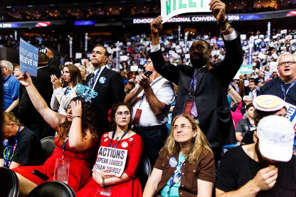 Photo - Pennsylvania supporters for former Democratic presidential candidate Sen. Bernie Sanders, I-Vt, sit while others cheer for Democratic presidential nominee Hillary Clinton during the second day of the Democratic National Convention in Philadelphia, Tuesday, July 26, 2016. (James Robinson/PennLive.com via AP)