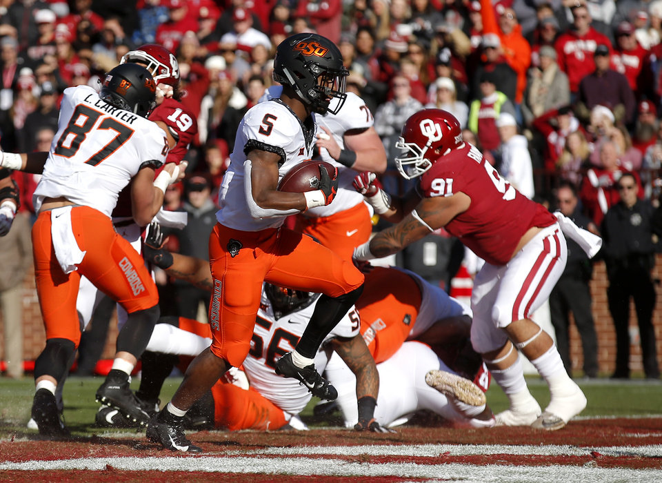 Photo - Oklahoma State's Justice Hill (5) scores a touchdown in the first quarter during a Bedlam college football game between the University of Oklahoma Sooners (OU) and the Oklahoma State University Cowboys (OSU) at Gaylord Family-Oklahoma Memorial Stadium in Norman, Okla., Nov. 10, 2018.  Photo by Sarah Phipps, The Oklahoman