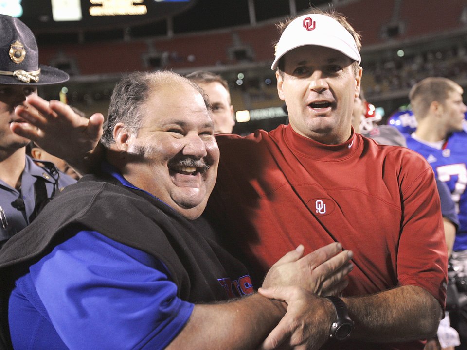Photo - Kansas head coach Mark Mangino, left, and Oklahoma head coach Bob Stoops hug after OU defeated Kansas 19-3, in the University of Oklahoma Sooners (OU) college football game against Kansas (KU), at Arrowhead Stadium, Saturday, October 15, 2005, in Kansas City, Missouri. by Bill Waugh/The Oklahoman