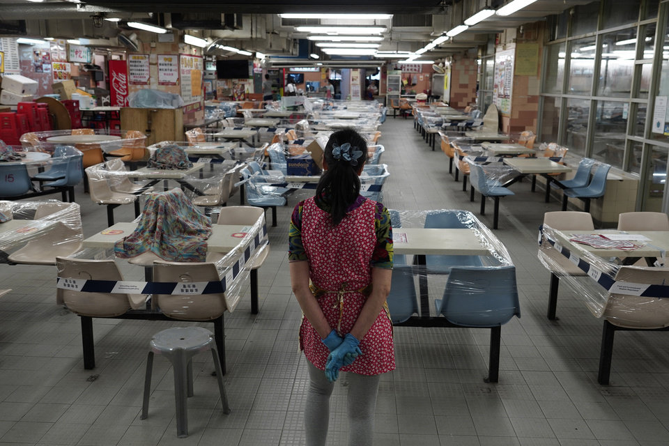 Photo -  A restaurant employee looks at empty sits at a Chinese food court in Hong Kong, Wednesday, July 29, 2020. Hong Kong has banned dining-in at restaurants completely on Wednesday and make it mandatory to wear masks in all public places, as the city battles its worst coronavirus outbreak to date. (AP Photo/Vincent Yu)