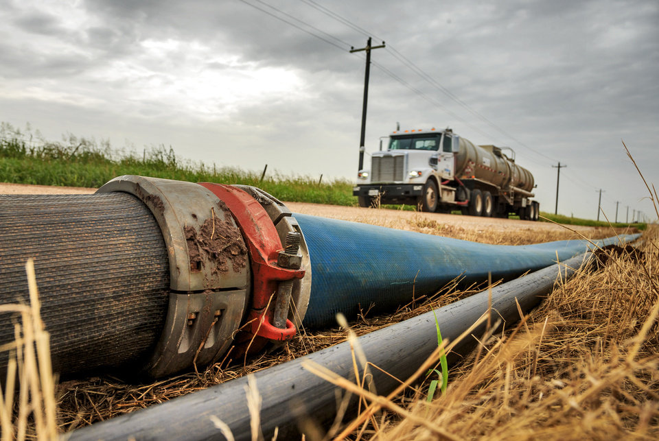 Photo -  A lay-flat hose to pump water to oil production sights runs along the roadway near Kingfisher. [Photo by Chris Landsberger, The Oklahoman]