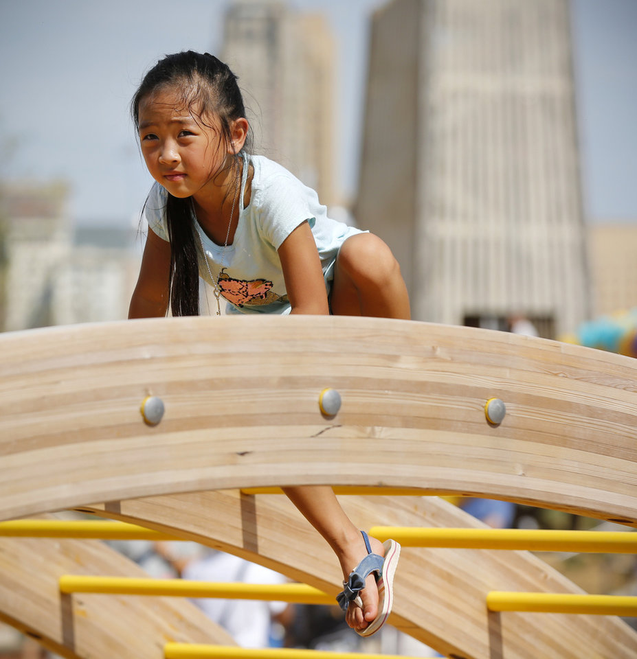 Photo - Ira Cunanan, 6, plays in the children's playground during the grand opening weekend of Scissortail Park in Oklahoma City, Saturday, Sept. 28, 2019. [Nate Billings/The Oklahoman]