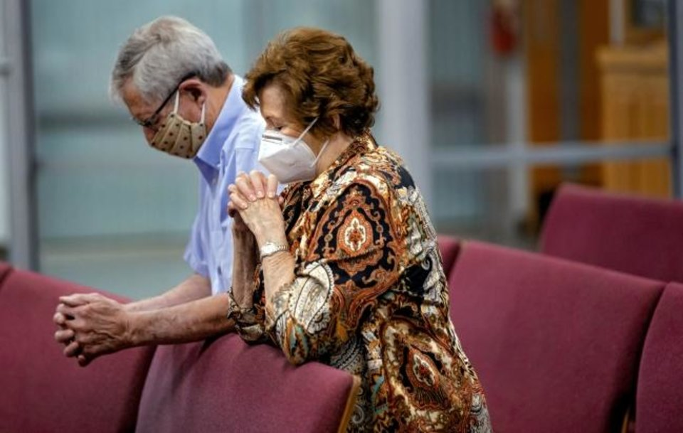 Photo -  Parishioners James and Dana Spencer pray during Mass at Holy Spirit Catholic Church in Mustang. [Chris Landsberger/The Oklahoman]