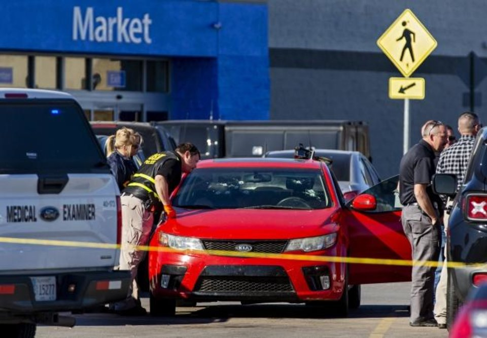 Photo -  Members of the Oklahoma State Bureau of Investigation work the scene of a shooting that left three people dead in the Walmart parking lot in Duncan on Monday. [Chris Landsberger/The Oklahoman]